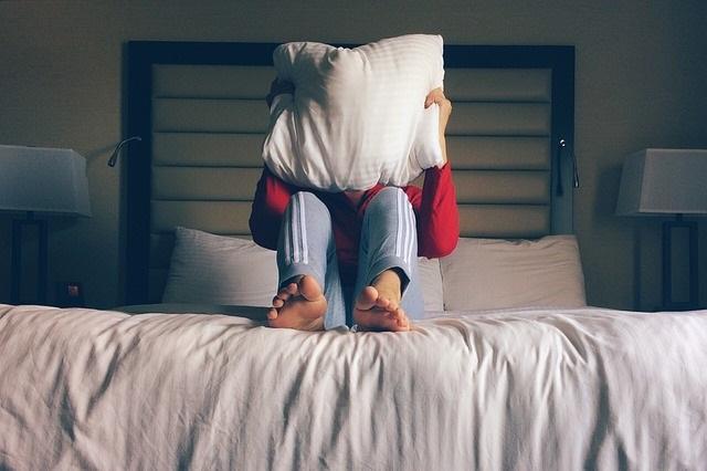 Człowiek siedzący na łóżku i przykrywający się poduszką